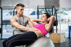 Male trainer assisting woman with sit ups. Male trainer assisting women with sit ups at crossfit gym Royalty Free Stock Photography