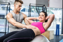 Male trainer assisting woman with sit ups Stock Image