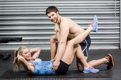 Male trainer assisting woman with sit ups. Male trainer assisting women with sit ups at crossfit gym Stock Image