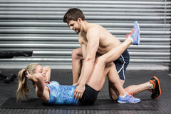 Male trainer assisting woman with sit ups. Male trainer assisting women with sit ups at crossfit gym Stock Images