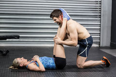 Male trainer assisting woman with sit ups. Male trainer assisting women with sit ups at crossfit gym Royalty Free Stock Image