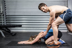 Male trainer assisting woman stretching. Male trainer assisting women stretching at crossfit gym Royalty Free Stock Photo