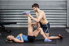 Male trainer assisting woman stretching. Male trainer assisting women stretching at crossfit gym Royalty Free Stock Images