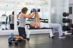 Male trainer assisting young man with dumbbells in gym. Side view of a male trainer assisting young men with dumbbells in the gym Royalty Free Stock Images