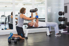 Male trainer assisting young man with dumbbells in gym. Side view of a male trainer assisting young men with dumbbells in the gym Stock Photos