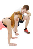Male trainer assisting young woman doing push-up Stock Photo
