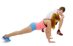 Male trainer assisting young woman doing push-up Stock Photography