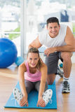 Male trainer assisting young woman with pilate exercises Stock Photography