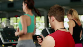 Male trainer checking treadmill performance. In crossfit gym stock footage