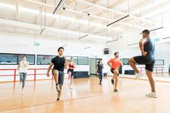 Trainer And Clients Doing High Knee Running While Performing Aerobics. Male trainer and clients doing high knee running while performing aerobics in gym stock photography