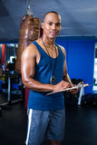Male trainer with clipboard in gym. Portrait of male trainer with clipboard standing in gym Royalty Free Stock Images