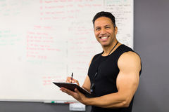 Male trainer clipboard. Professional middle aged male trainer writing on clipboard Stock Image