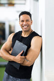 Male trainer clipboard. Smiling male trainer with clipboard standing in gym Royalty Free Stock Images