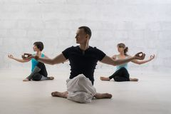 Male trainer doing yoga view against brick wall Stock Image