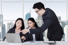 Male trainer explaining a job in office. Young caucasian trainer pointing at laptop to explain a job on his employees in the office Royalty Free Stock Photo