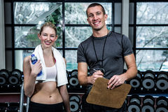 Male trainer and fit woman smiling. Male trainer and fit women smiling at gym Stock Photography
