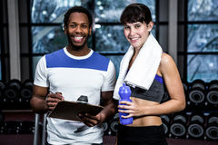 Male trainer and fit woman smiling. Male trainer and fit women smiling at gym Stock Images