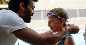 Male trainer giving gold medal to his student. Near poolside stock video footage