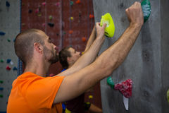 Male trainer guiding athlete in climbing wall at health club Royalty Free Stock Photo