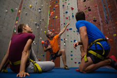 Male trainer guiding athletes in wall climbing at gym. Low angle view of male trainer guiding athletes in wall climbing at gym Royalty Free Stock Photo