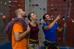 Male trainer guiding athletes in wall climbing. At health club Stock Image