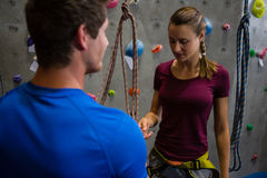 Male trainer guiding female athlete in climbing wall Stock Images