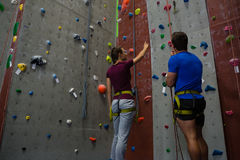 Male trainer guiding woman in climbing wall at club Royalty Free Stock Images