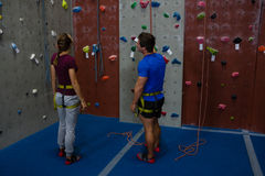 Male trainer guiding woman in climbing wall at gym Royalty Free Stock Images