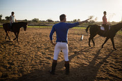 Male trainer guiding young women in riding horse. At barn Stock Image