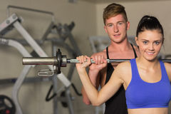 Male trainer helping fit woman to lift the barbell in gym. Portrait of a young male trainer helping young fit women to lift the barbell in the gym Royalty Free Stock Image