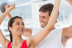 Male trainer helping fit woman to lift the barbell. Happy male trainer helping young fit women to lift the barbell in the gym Stock Images