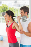Male trainer helping fit woman to lift the barbell. Male trainer helping young fit women to lift the barbell in the gym Royalty Free Stock Images