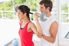 Male trainer helping fit woman to lift the barbell. Male trainer helping young fit women to lift the barbell in the gym Stock Photo