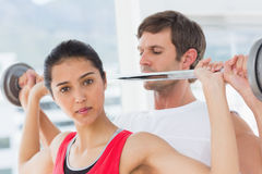 Male trainer helping fit woman to lift the barbell Stock Photo