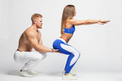 Male trainer helping sexy woman doing squats. Male trainer helping sexy women doing squats isolated on white background Royalty Free Stock Images
