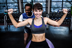 Male trainer helping woman during dumbbells exercise. Male trainer helping women during dumbbells exercise at gym Stock Photography