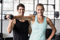 Male trainer helping woman with the dumbbells. Male trainer helping women with the dumbbells in crossfit gym Royalty Free Stock Photography