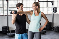 Male trainer helping woman with the dumbbells. Male trainer helping women with the dumbbells in crossfit gym Royalty Free Stock Image