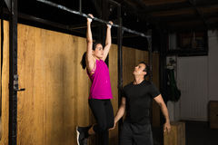 Male trainer helping a woman at the gym. Handsome young Latin trainer and coach helping a women do some pull-ups in a cross-training gym Stock Photography