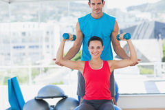 Male trainer helping woman with her exercises at gym. Portrait of a male trainer helping women with her exercises at a bright gym Royalty Free Stock Photography