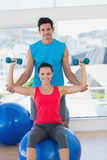 Male trainer helping woman with her exercises at gym. Portrait of a male trainer helping women with her exercises at a bright gym Stock Photography