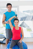 Male trainer helping woman with her exercises at gym. Portrait of a male trainer helping women with her exercises at a bright gym Royalty Free Stock Photo