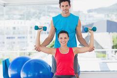 Male trainer helping woman with her exercises at gym. Portrait of a male trainer helping women with her exercises at a bright gym Royalty Free Stock Images
