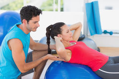 Male trainer helping woman with her exercises at gym. Side view of a male trainer helping women with her exercises at a bright gym Royalty Free Stock Photography