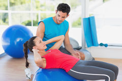 Male trainer helping woman with her exercises at gym. Side view of a male trainer helping women with her exercises at a bright gym Royalty Free Stock Photo