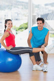 Male trainer helping woman with her exercises at gym. Smiling male trainer helping women with her exercises at a bright gym Royalty Free Stock Images