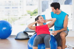 Male trainer helping woman with her exercises at gym. Smiling male trainer helping women with her exercises at a bright gym Stock Photo