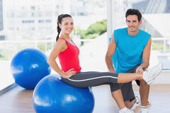 Male trainer helping woman with her exercises at gym. Smiling male trainer helping women with her exercises at a bright gym Royalty Free Stock Photo