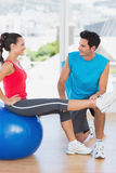 Male trainer helping woman with her exercises at gym. Smiling male trainer helping women with her exercises at a bright gym Royalty Free Stock Photos