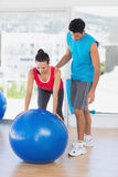 Male trainer helping woman with her exercises at gym. Male trainer helping women with her exercises at a bright gym Stock Images